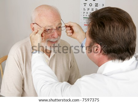 Optician putting a new pair of reading glasses on a patient. - stock photo