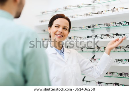 optician showing glasses to man at optics store