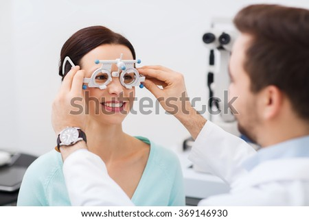 optician with trial frame and patient at clinic - stock photo