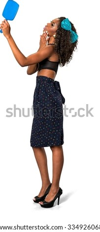 Optimistic African woman with medium dark brown hair in casual outfit using hand mirror - Isolated