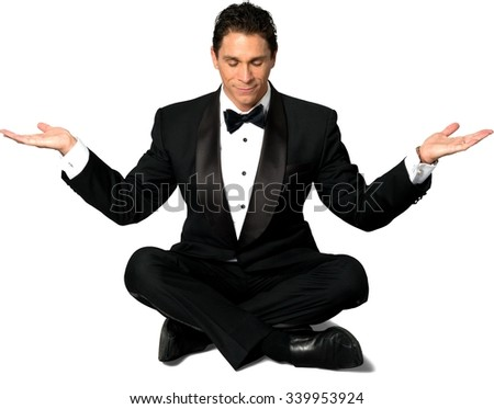 Optimistic Caucasian man with short black hair in a tuxedo with meditation hands - Isolated - stock photo