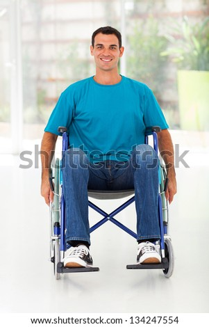 optimistic handicapped man sitting on wheelchair - stock photo