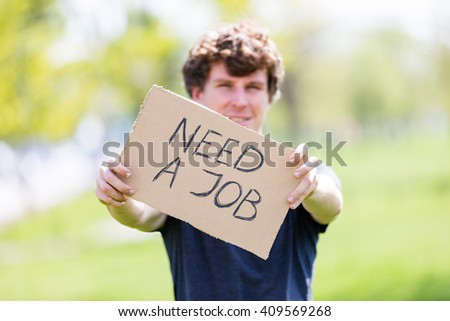 "Optimistic man holding ""need a job"" cardboard sign, unemployment concept"
