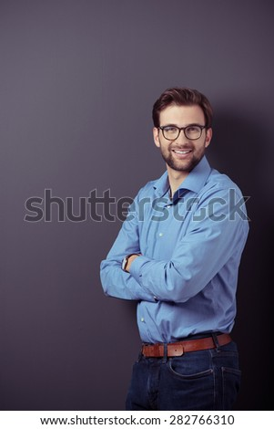 Optimistic Portrait of a Handsome Young Businessman Standing Against Gray Wall with Copy Space While Looking at the Camera with Arms Crossing Over her Stomach. - stock photo