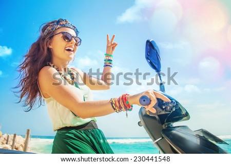 optimistic pretty hippie woman riding her motorbike - stock photo