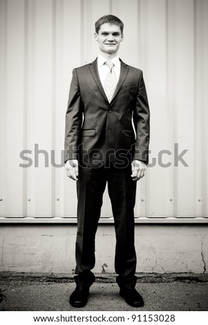 Optimistic Young man standing against wall - b&w version - stock photo