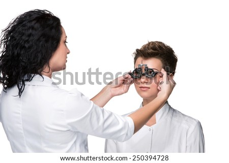 Optometrist holding an eye test glasses and giving to young woman eye examination. Isolate on white background  - stock photo
