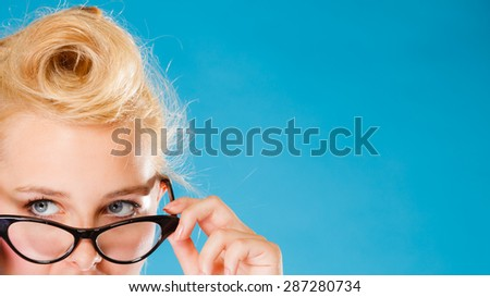 Optometrist, oculist and ophthalmologist concept. Young blonde woman with eyeglasses on blue background in studio. - stock photo