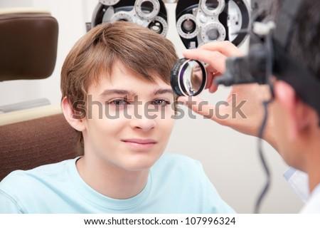Optometrist taking an eyesight test examination. - stock photo