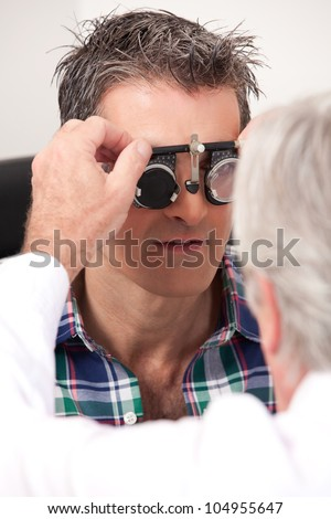 Optometrist using measuring spectacles on patient