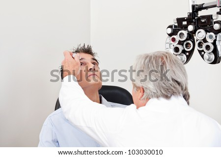 Optometrist using mydriatics eye drops to numb the eyes of his patient for further tests - stock photo