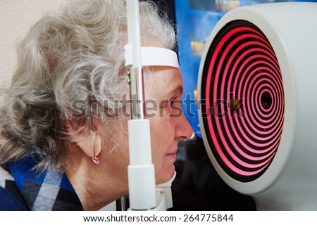 Optometry and ophthalmology.  senior woman patient under sight testing or eye examinations in clinic - stock photo