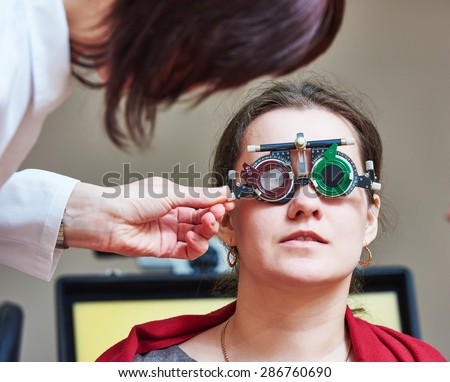 Optometry concept. female doctor ophthalmologist or optometrist helps young woman with phoropter during sight testing or eye examinations in clinic - stock photo