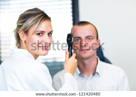 Optometry concept - handsome young man having her eyes examined by an eye doctor - stock photo