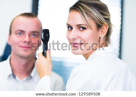 Optometry concept - handsome young man having his eyes examined by an eye doctor (color toned image; shallow DOF) - stock photo
