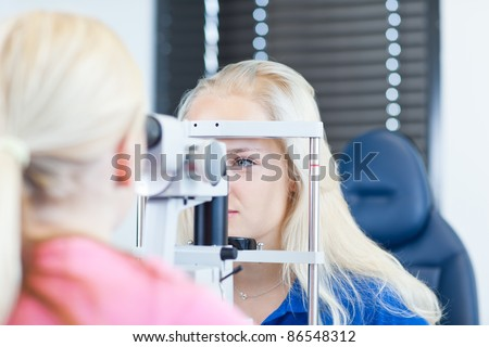 optometry concept - pretty, young female patient having her eyes examined by an eye doctor (color toned image; shallow DOF) - stock photo
