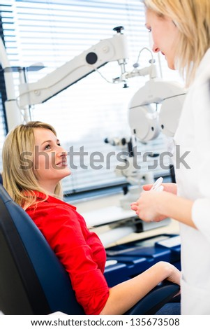 Optometry concept - pretty young woman having her eyes examined by an eye doctor (color toned image; shallow DOF) - stock photo