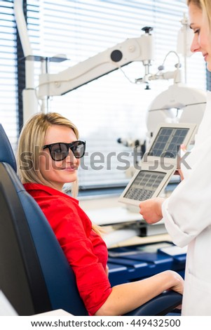 Optometry concept - pretty young woman having her eyes examined by an eye doctor (color toned image; shallow DOF)