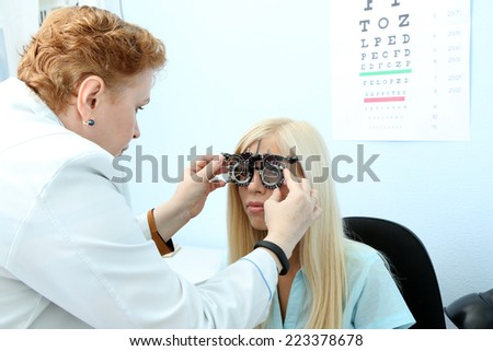 Optometry concept - pretty young woman having her eyes examined by eye doctor  - stock photo