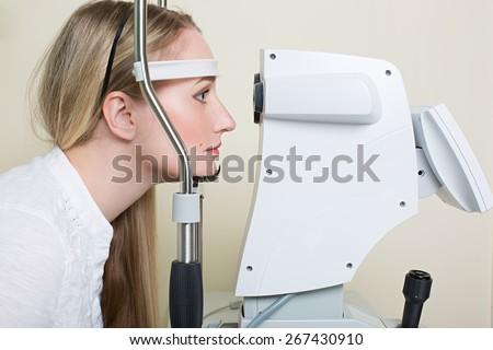 Optometry concept -  young woman having her eyes examined by an eye handsome elderly doctor. Topography of the cornea - stock photo