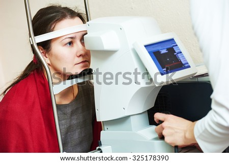 optometry. Young woman patient under eyesight examination in eye ophthalmological clinic  - stock photo