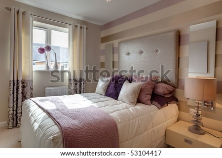 Opulent modern bedroom with fashionable oversized headboard and brightly colored fabrics - stock photo