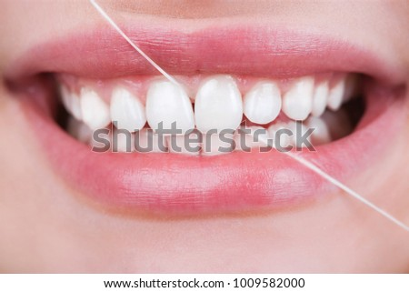 Oral hygiene and health care. Smiling women use dental floss white healthy teeth.