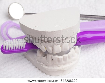 Oral hygiene health concept. Closeup blue toothbrush mirror and tongue cleaner with dental gypsum model - stock photo