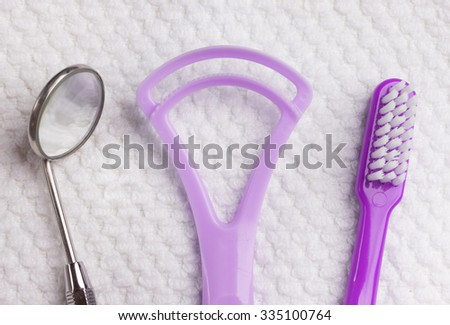 Oral hygiene health concept. Closeup dental tools violet toothbrush mirror and tongue cleaner on white towel - stock photo