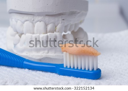 Oral hygiene health concept. Closeup toothbrush with paste in dental gypsum model plaster - stock photo