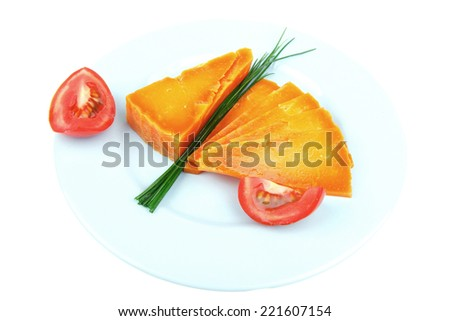 orange aged delicious cheddar cheese chop with slice on blue plate with tomatoes and chives isolated over white background
