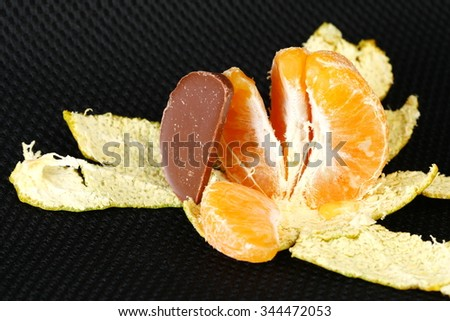 Orange and a piece of chocolate represent the fruit concept related idea.