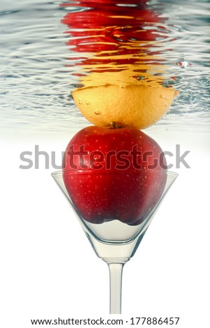 Orange and  apple in martini glass with reflection.