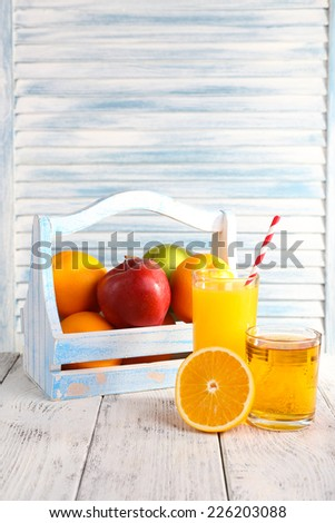 Orange and apple juice and fresh fruits in wooden box on wooden table on wooden wall background - stock photo