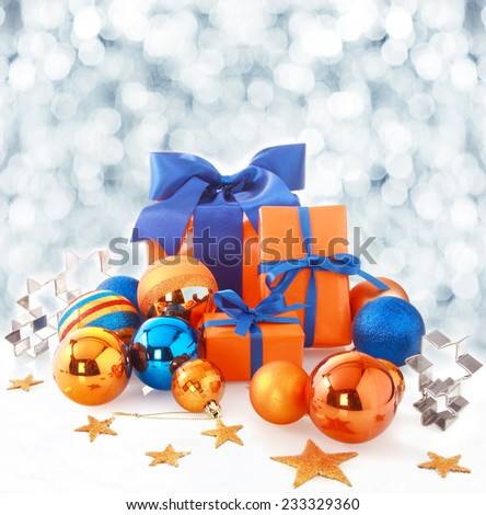 Orange and blue Christmas background with color themed gifts and baubles arranged with stars and cookie cutters against a backdrop of falling winter snowflakes in a sparkling bokeh with copyspace - stock photo