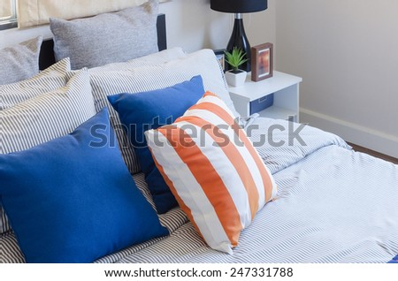 orange and blue pillows on bed at home - stock photo