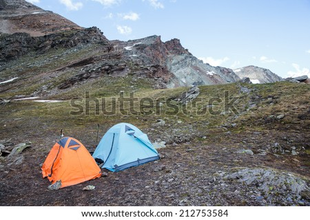 Orange and blue tents in the mountains - stock photo