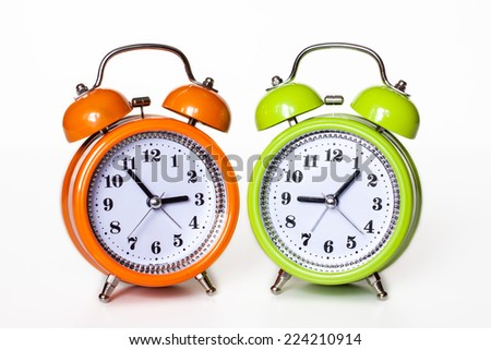 Orange and Green  alarm clocks on white background. Colorful life style. Happy hours.
