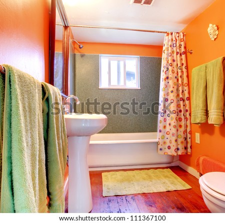 Orange and green bathroom with tub, sink  and wood floor. - stock photo