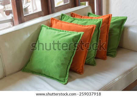 Orange and green Decorative pillows on white leather sofa