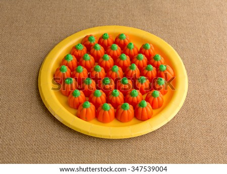 Orange and green Halloween pumpkin candy on a yellow paper plate atop a burlap tablecloth illuminated with natural light. - stock photo