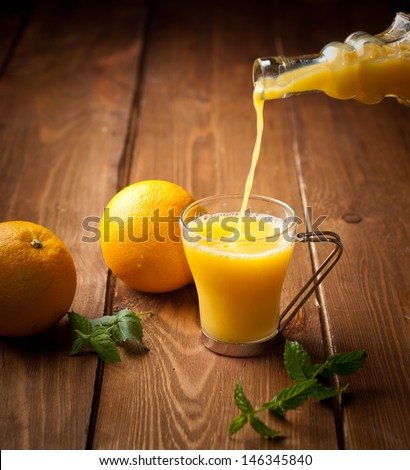 Orange and orange juice on a wooden background - stock photo