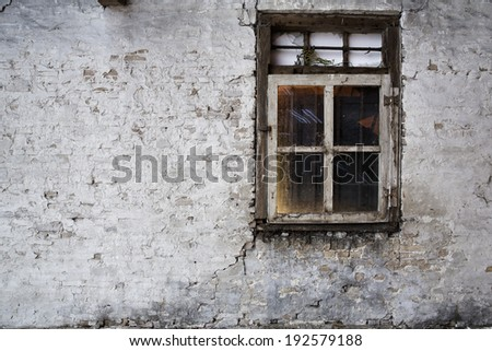 Orange and red lit vintage, old window in an ancient white brick wall in an abandoned farm barn, with room for copy space - stock photo