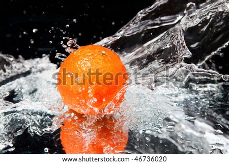 Orange and splash water over black background - stock photo