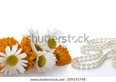 Orange and white flowers and pearl necklace on a light background. Space for text. - stock photo