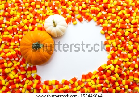 Orange and white pumpkins in white square on candy corn background - stock photo