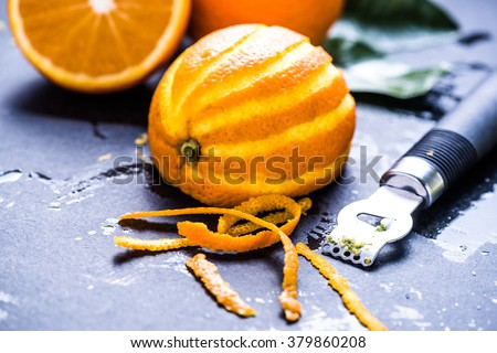 Orange and zest, natural refreshing ingredients on dark slate. - stock photo