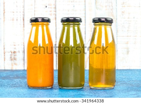 orange apple and kiwi Juice bottle on a wooden background.
