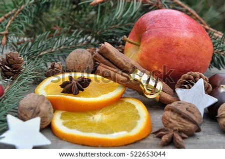 orange, apple, walnuts and spices on wooden background with Christmas decoration