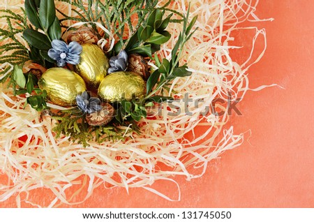 Orange background with arrangement with golden eggs and nest in the corner - stock photo